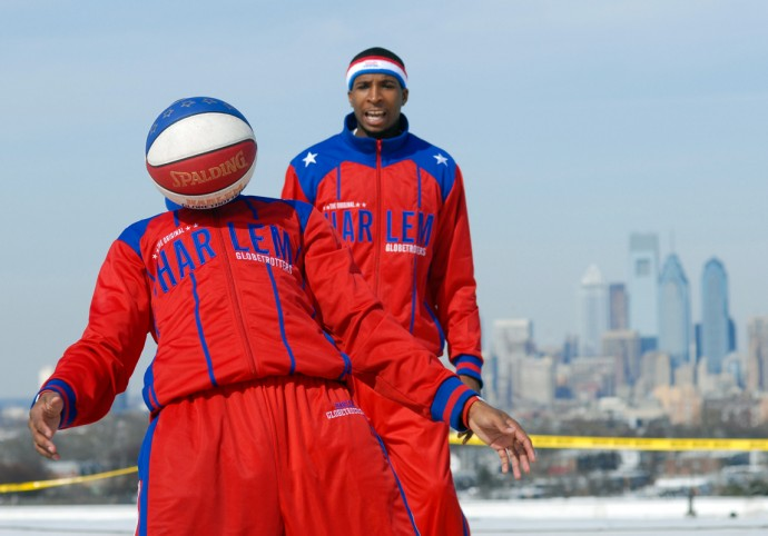 Harlem Globetrotters' Scooter Christensen (L) controls the basketball with his body as Bam Bam Bamiro looks on during a game March 5, 2009 on the rooftop of the Wachovia Spectrum. The Harlem Globetrotters played the Washington Generals in a 'Remember the Spectrum' rooftop game. The Spectrum is scheduled to be torn down and replaced with a shopping complex. (Photo by William Thomas Cain/cainimages.com)