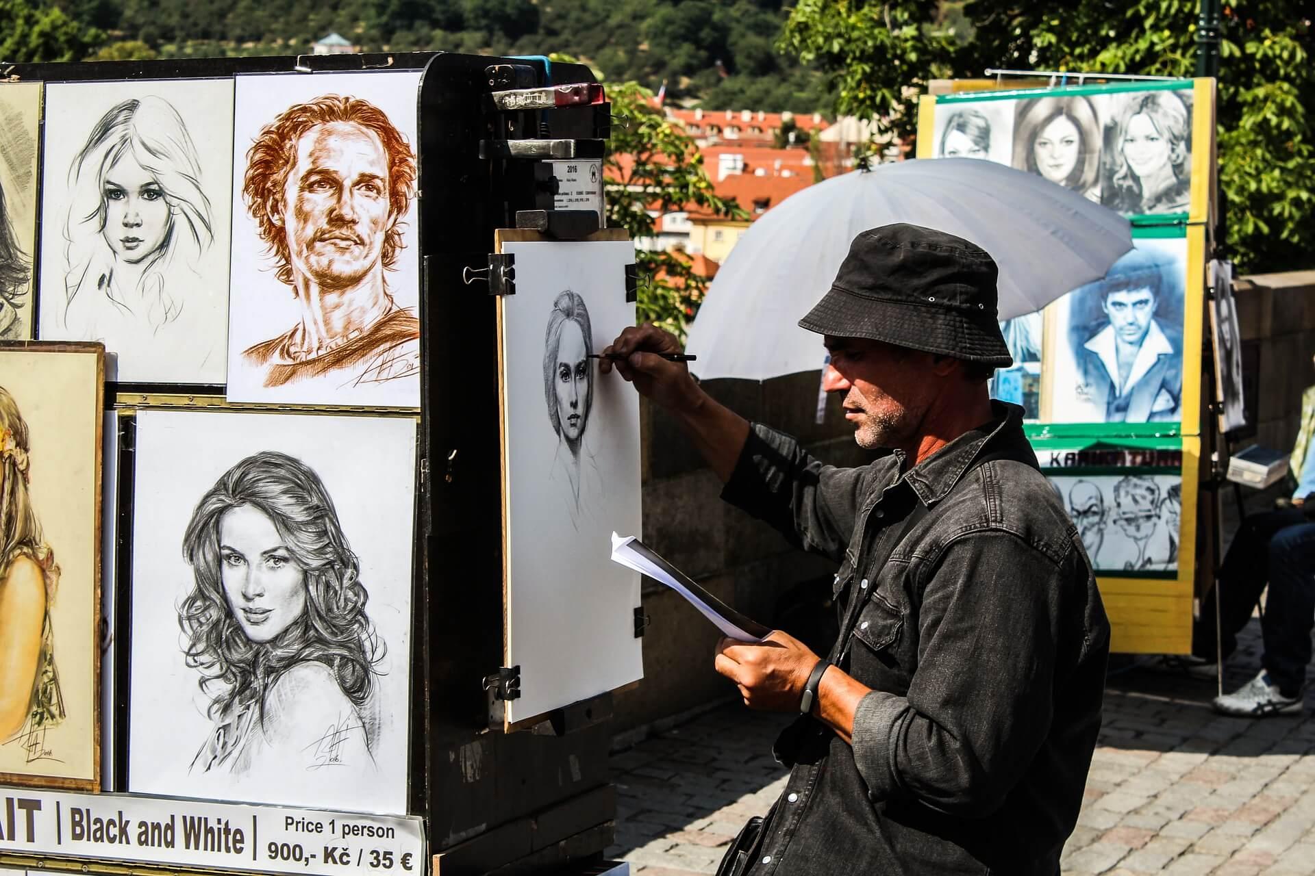 A man painting portraits.